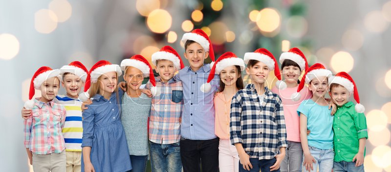 Stock image of 'childhood, christmas, holidays and people concept - happy smiling children in santa hats hugging over lights background'