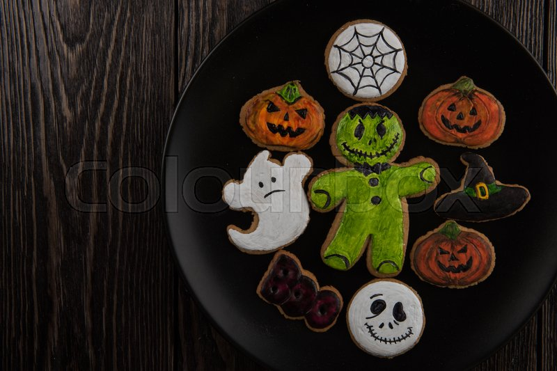 Stock image of 'Homemade delicious ginger biscuits for Halloween on wooden table'