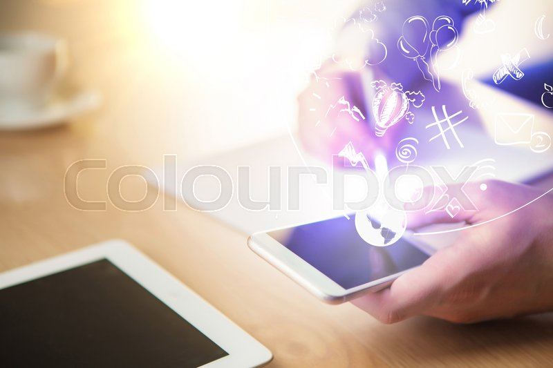 Stock image of 'The male hand holding a phone and hand writing against the background of the office and laptop'