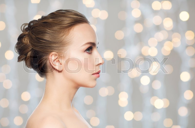 Stock image of 'health, people, plastic surgery and beauty concept - beautiful young woman face profile over holidays lights background'