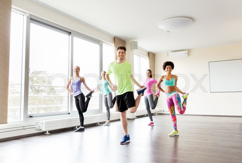 Stock image of 'fitness, sport, training and lifestyle concept - group of smiling people with trainer exercising and stretching legs in gym'