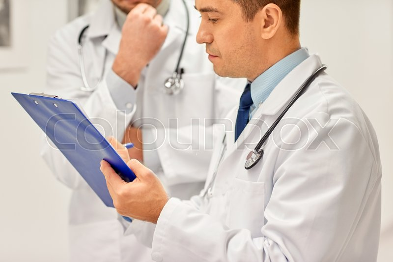 Stock image of 'clinic, profession, people, healthcare and medicine concept - close up of doctors with clipboard at hospital'