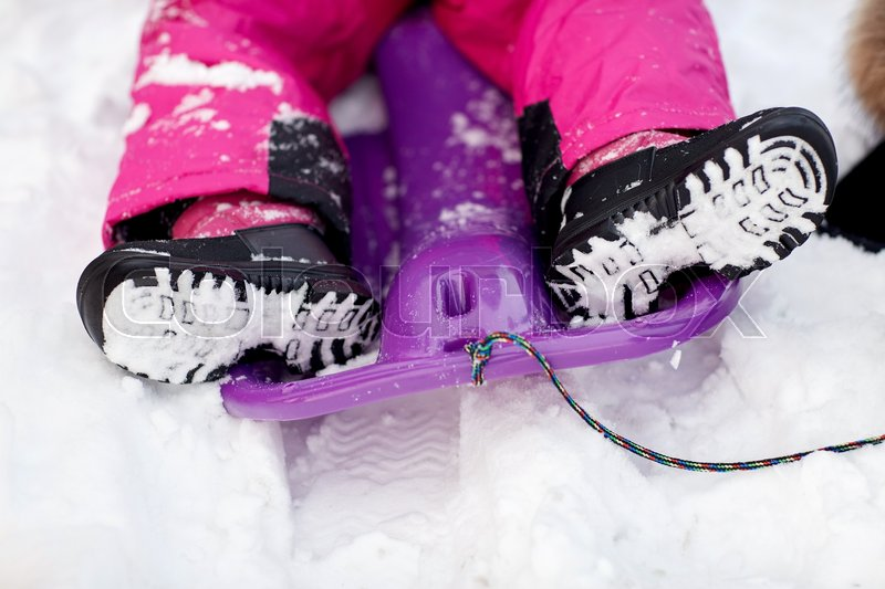 Stock image of 'childhood, footwear, fashion, season and people concept - close up of kids feet in winter boots on sled'