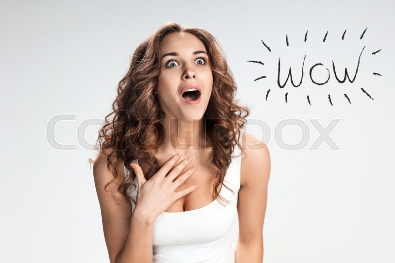 Stock image of 'Portrait of young woman with shocked facial expression  over gray background'