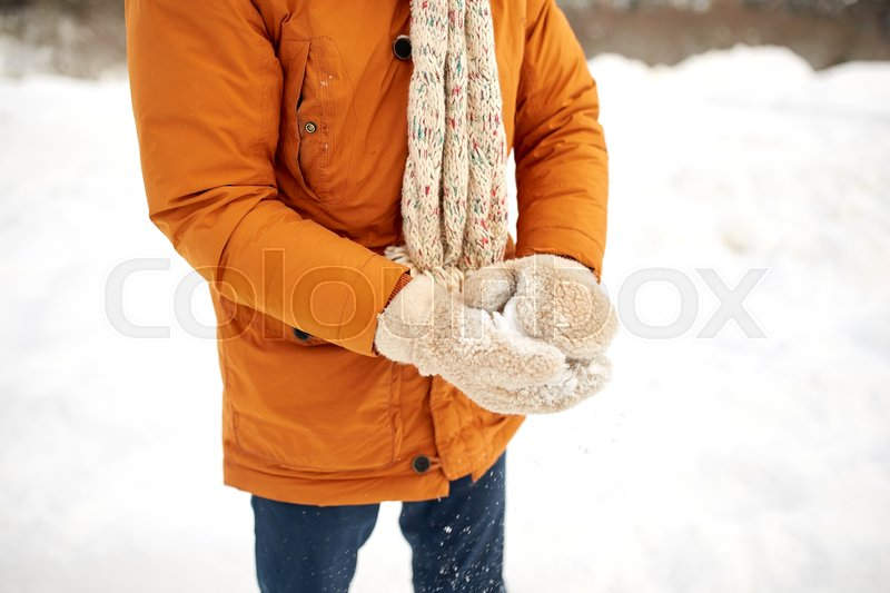Stock image of 'people, season, christmas, winter and snow concept - close up of man with snowball'