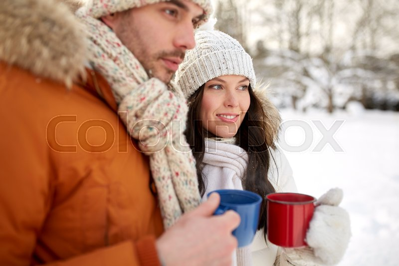Stock image of 'people, winter, drinks and season concept - close up of happy couple holding hot tea cups'