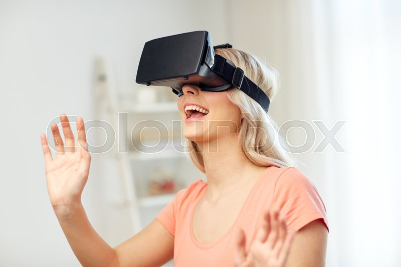 Stock image of 'technology, virtual reality, entertainment and people concept - happy young woman with virtual reality headset or 3d glasses playing game at home and touching something invisible'