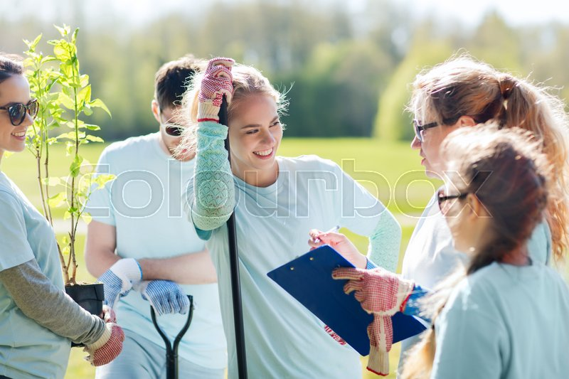 Stock image of 'volunteering, charity, people and ecology concept - group of volunteers with clipboard planting trees in park'