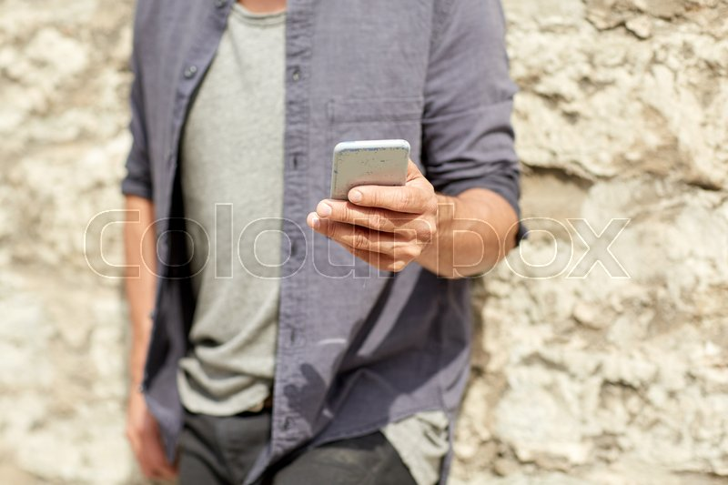 Stock image of 'leisure, technology, communication and people concept - close up of man with smartphone at stone wall on street'