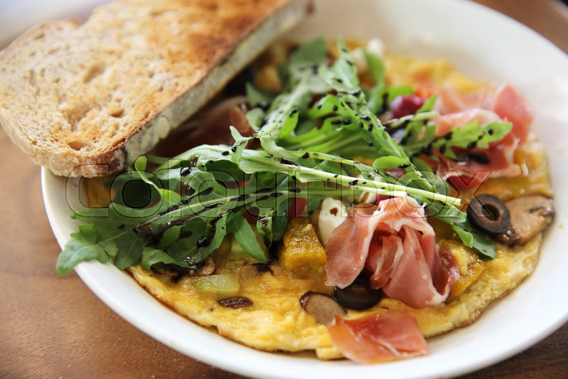 Stock image of 'Omelette with parma ham and salad'