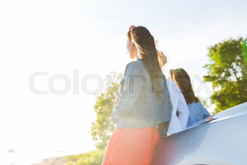 Stock image of 'summer vacation, holidays, travel, road trip and people concept - happy teenage girls or young women near car at seaside'