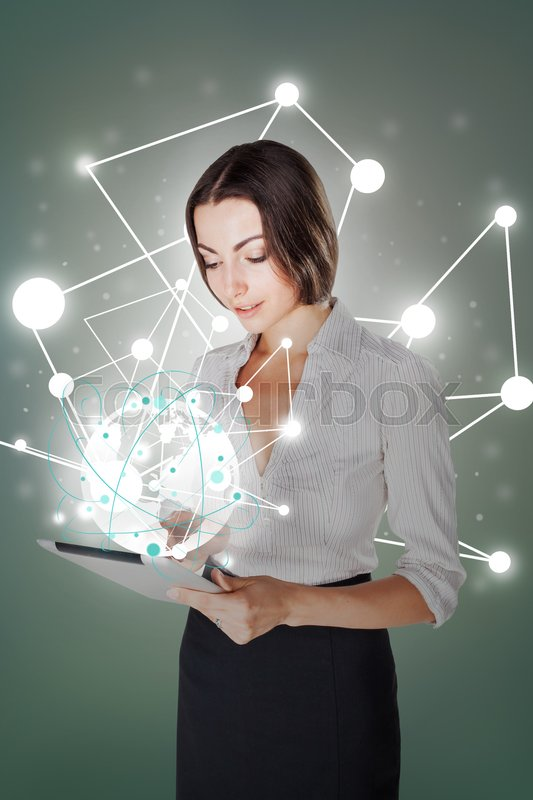 Stock image of 'Young business woman standing with laptop on gray background. Global wireless connection concept'