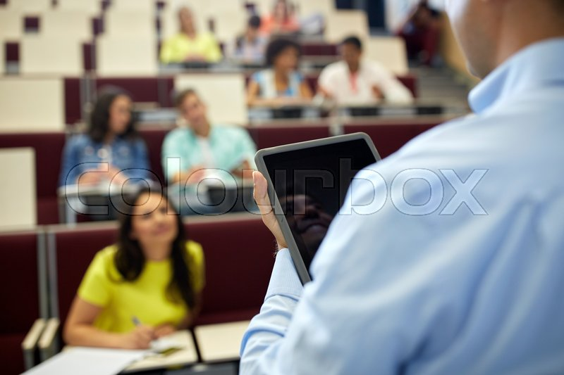 Stock image of 'education, high school, university, learning and people concept - close up of teacher with tablet pc computer and students at lecture hall'