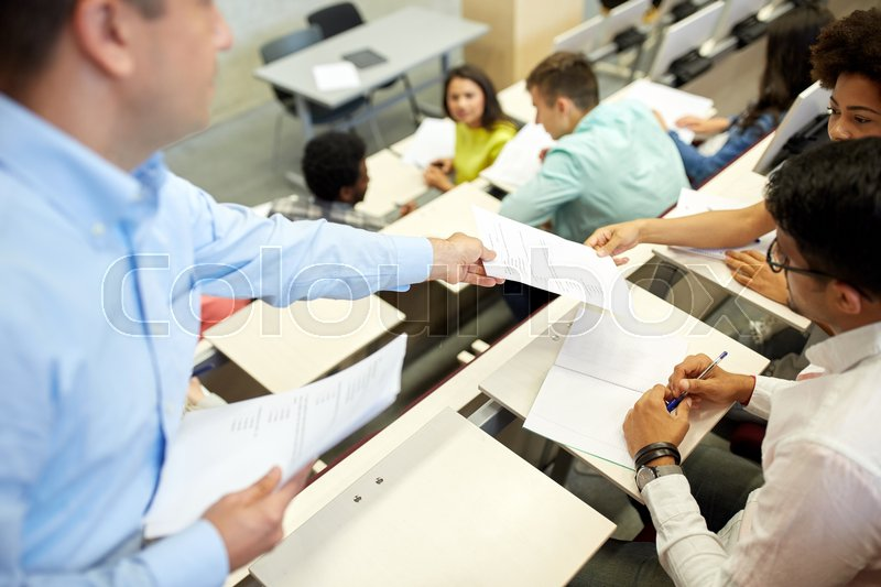 Stock image of 'education, high school, university, learning and people concept - teacher giving exam tests to students at lecture hall'