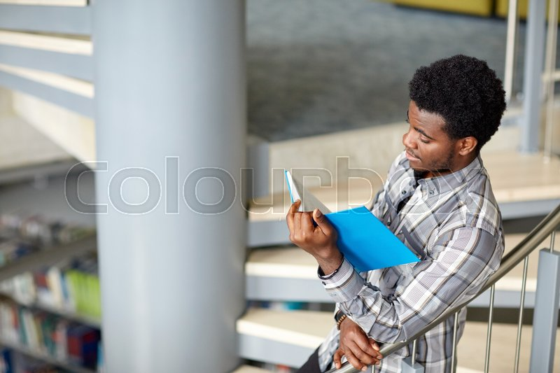 Stock image of 'education, high school, university, learning and people concept - happy african american student boy or young man reading book on stairs at library'