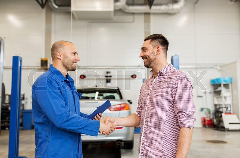 Stock image of 'auto service, repair, maintenance, gesture and people concept - mechanic with clipboard and man or owner shaking hands at car shop'