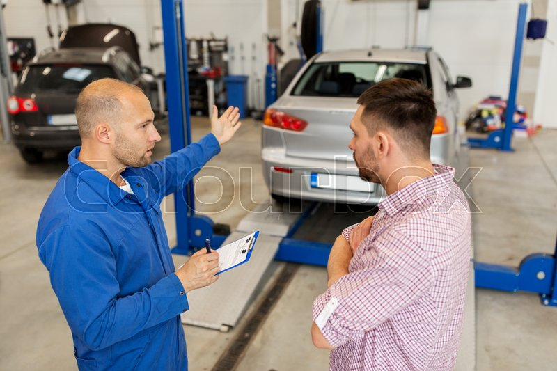 Stock image of 'auto service, repair, maintenance and people concept - mechanic with clipboard talking to man or owner at car shop'