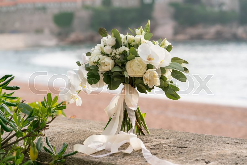 Bridal bouquet of orchids, ranunculuses, tulips and eucalyptus, white and green, stock photo