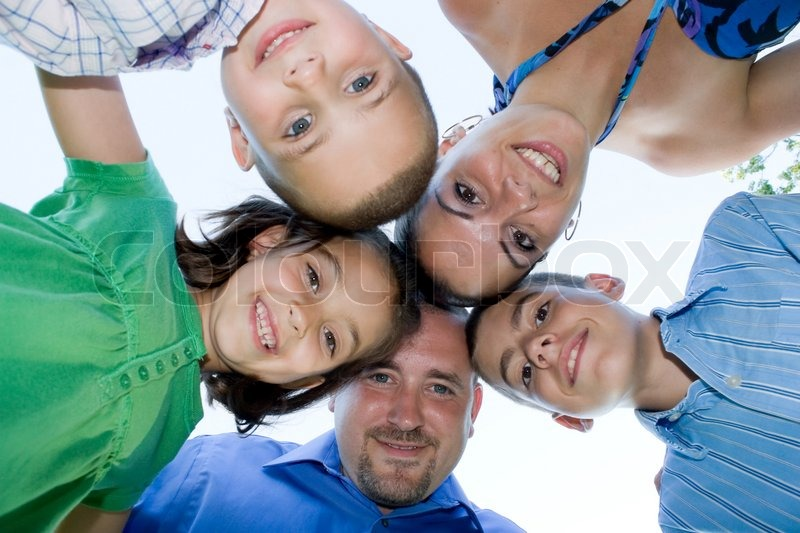 A happy family posing in a group huddle formation, stock photo