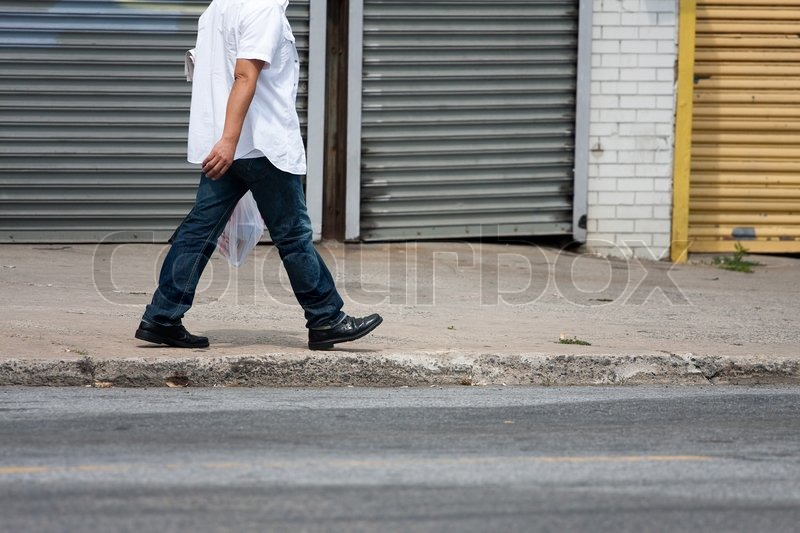One Man Walking Down The Sidewalk Along The Side Of The