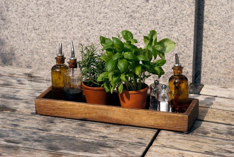 Basilikum, rosmarin , olie, eddike og urter udendørs i en trækasse ...