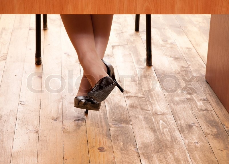 Female Foots In Shoes Looking Out From Under A Table