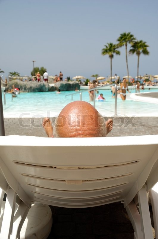 Bald Headed Man Relaxing By The Pool Stock Photo Colourbox