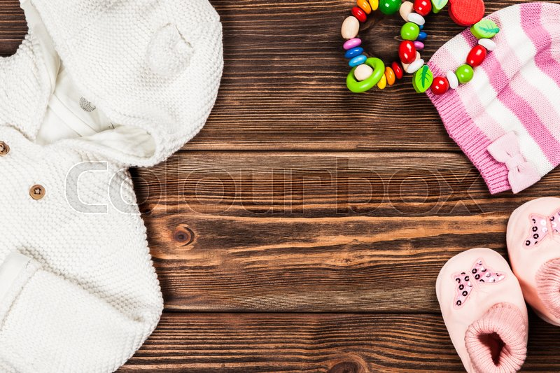 Baby clothes on wooden background.   Stock image   Colourbox