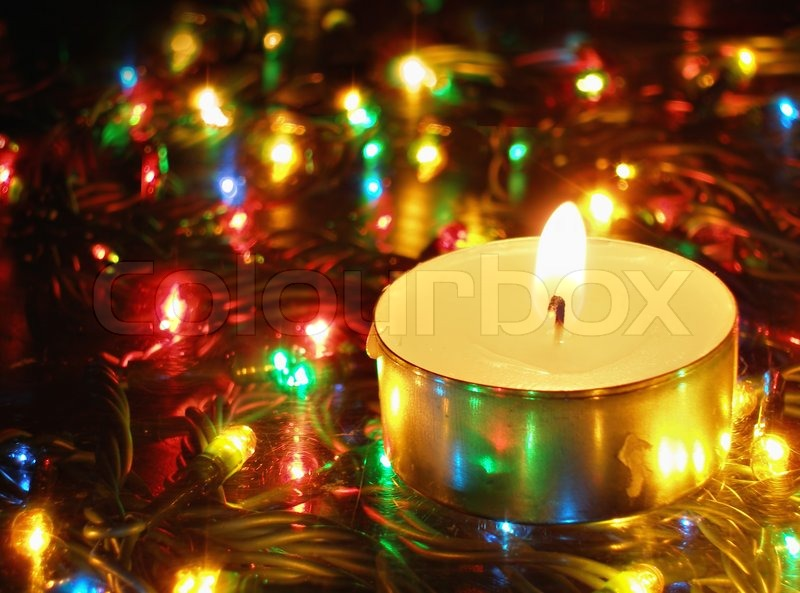 Candle with flame over colorful lights background | Stock Photo ...