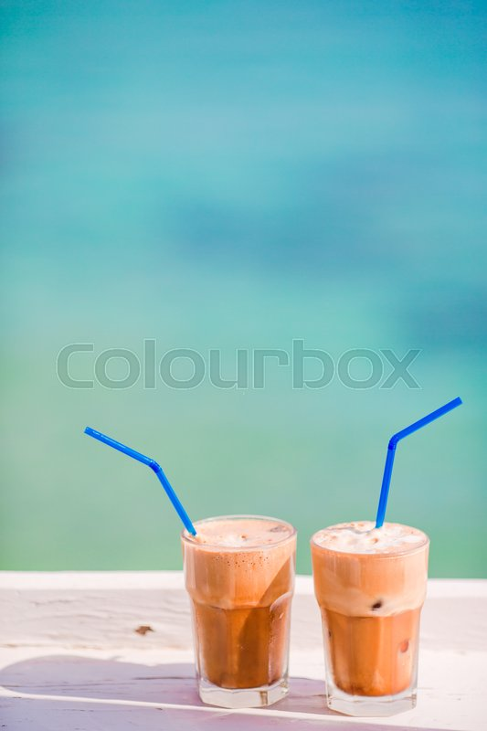 Frappe, ice coffee on the beach. Summer iced coffee frappuccino, frappe or latte in a tall glass background the sea in beach bar, stock photo