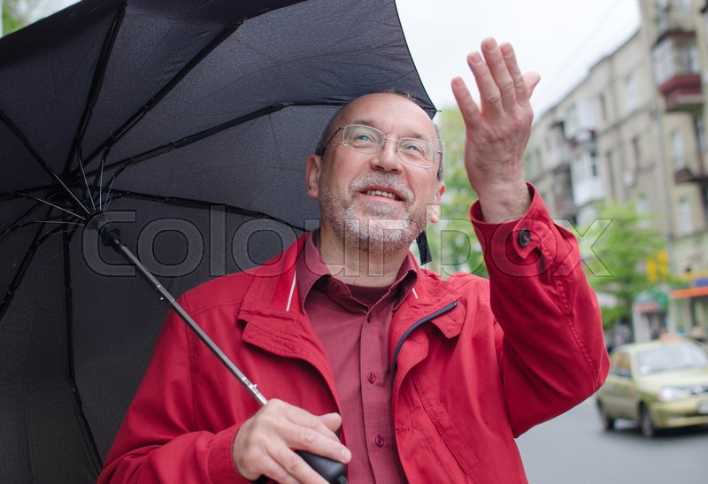 Aged man under the rain with umbrella, stock photo