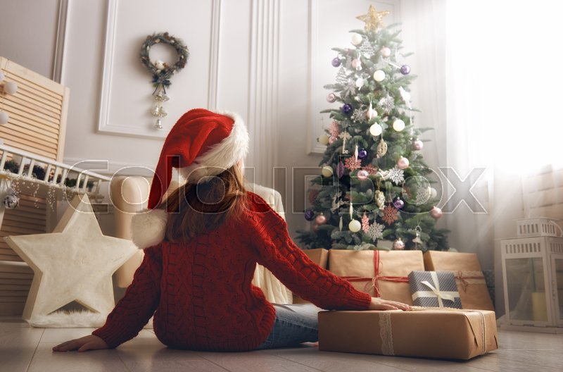 Merry Christmas and Happy Holidays! Cheerful cute little child girl with present. Kid holds a gift box near Christmas tree indoors, stock photo