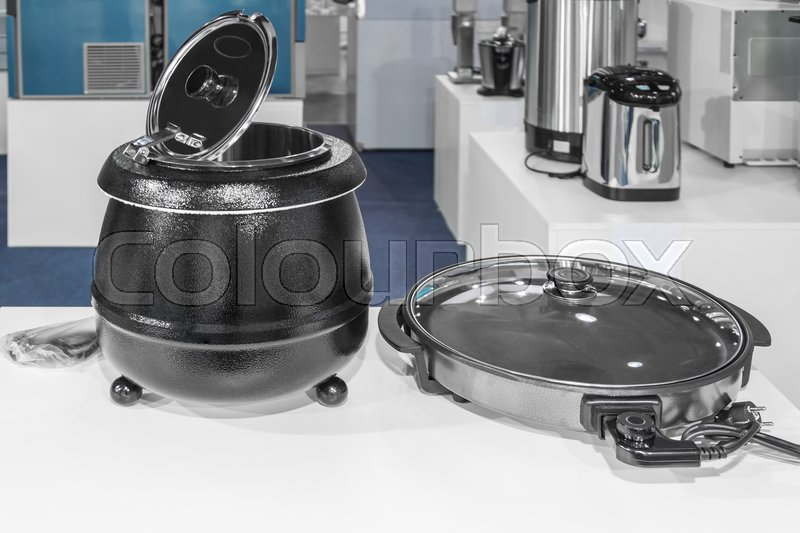 Electrical kitchen equipment, electric pressure cooker and frying pan in the foreground, stock photo
