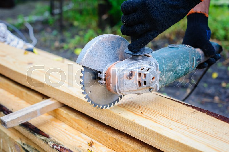 Men Use Hand Held Power Saw to Cut Planks of Wood for Home Construction, stock photo