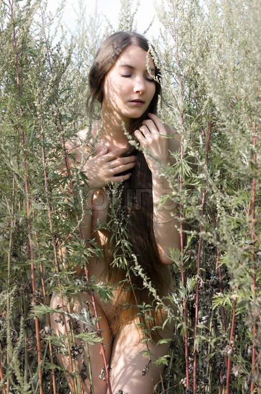 Very cute naked woman in nature cuddling watch