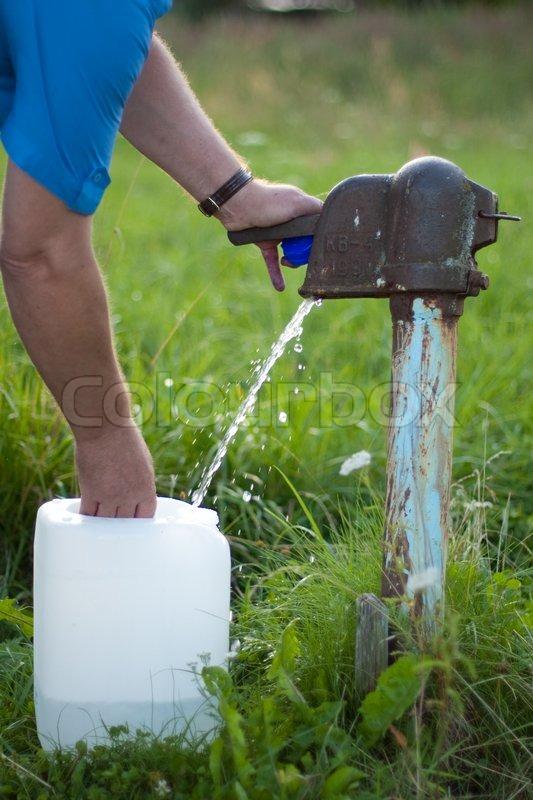 Alvorlig En mand samler vandet fra gammeldags   Stock foto   Colourbox VK77