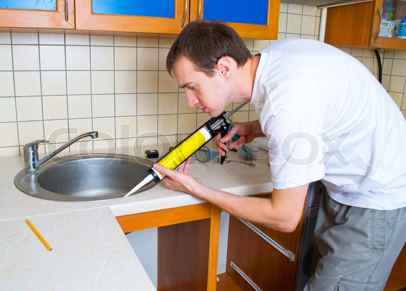 Plumber putting a silicone sealant to installing a kitchen sink ...
