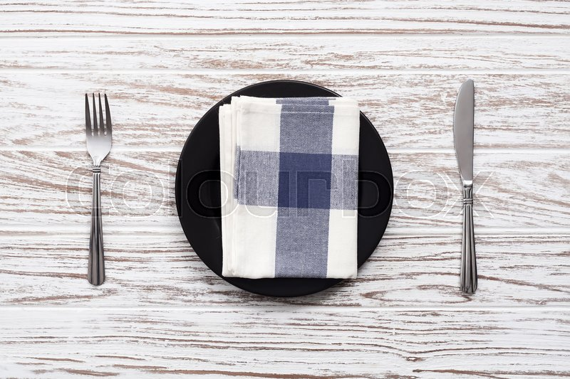 Empty plate napkin fork knife silverware white wooden table background still life vintage flat lay, stock photo