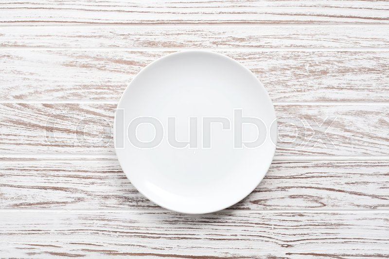 Empty plate on white wooden table background still life vintage flat lay, stock photo