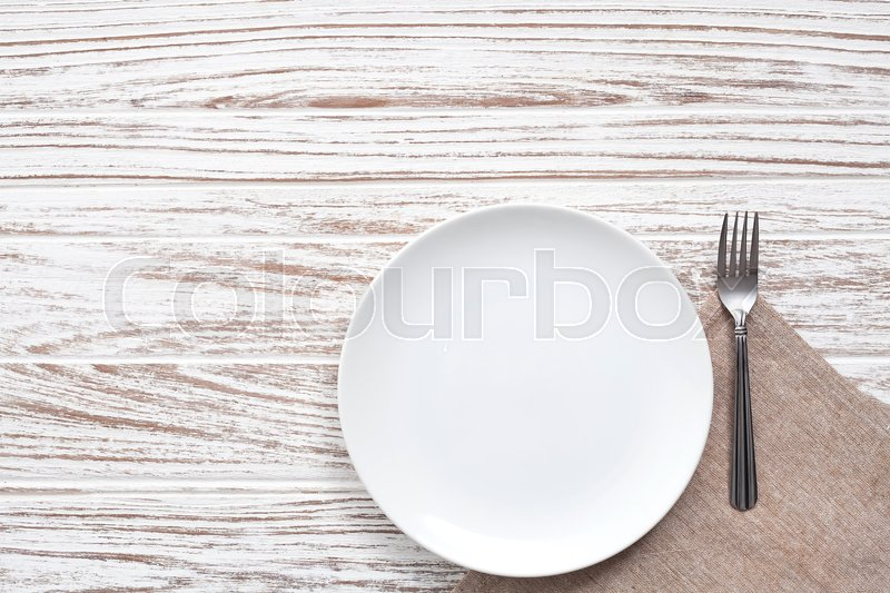 Empty plate napkin fork silverware white wooden table background still life vintage flat lay, stock photo