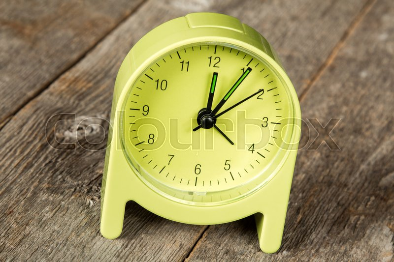 green alarm clock showing five minute past twelve hour stock photo colourbox