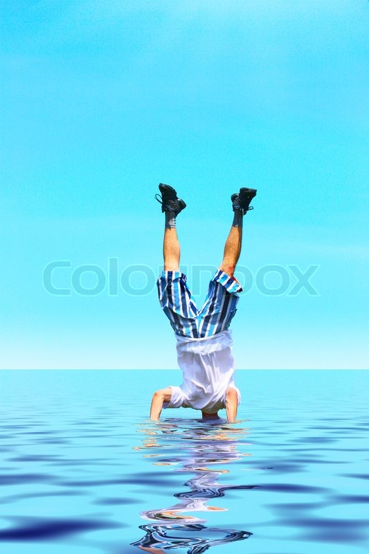 Crazy man stand upside down with head under water, stock photo