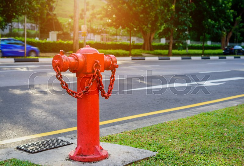 Red fire hydrant water pipe near the road. Fire hidrant for emergency fire access, stock photo