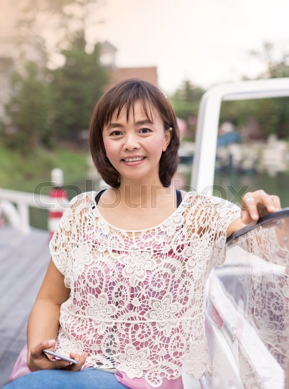 Middle Age Attractive Mature Asian Woman Relax Holding And Posing Look At Camera In Garden Stock Photo Colourbox