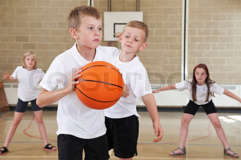 Elementary School Pupils Playing Basketball In Gym, stock photo