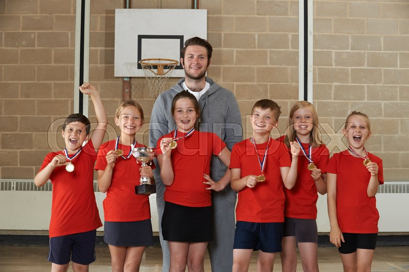 Victorious School Sports Team With Medals And Trophy In Gym, stock photo