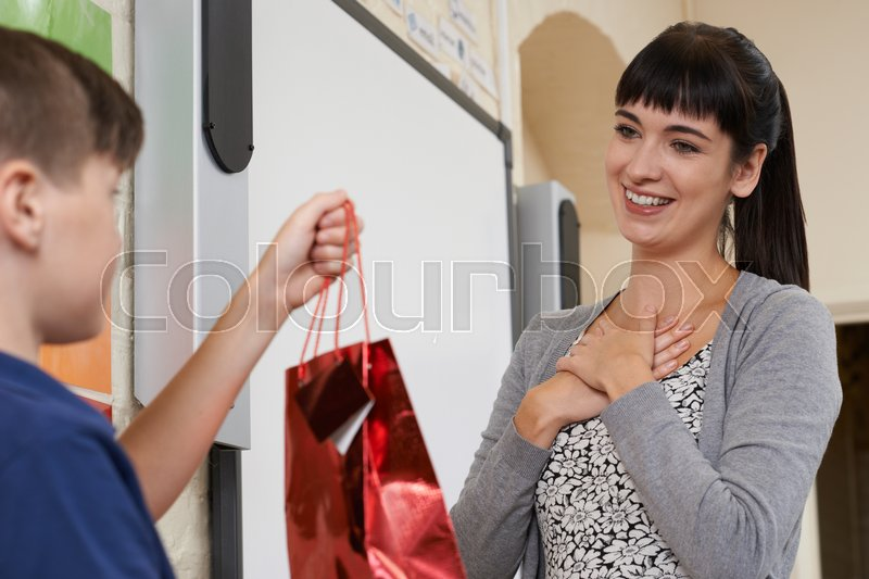 Male Pupil Giving Teacher End Of Term Gift, stock photo