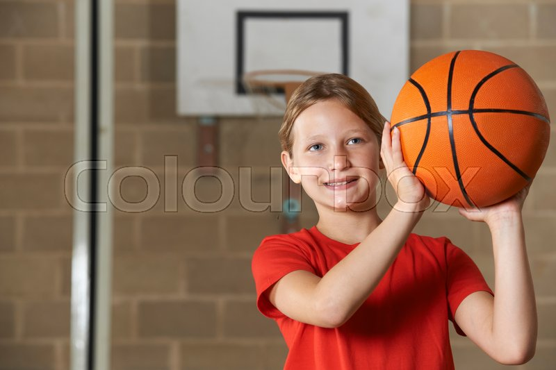 Girl Shooting Basketball In School Gym, stock photo