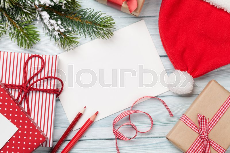 Christmas greeting card and gift boxes on wooden table. Top view with copy space. Gift wrapping, stock photo
