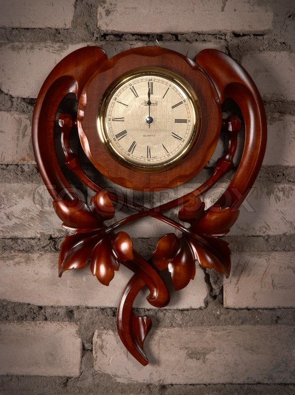 Old antique carved wooden clock on brick wall stock